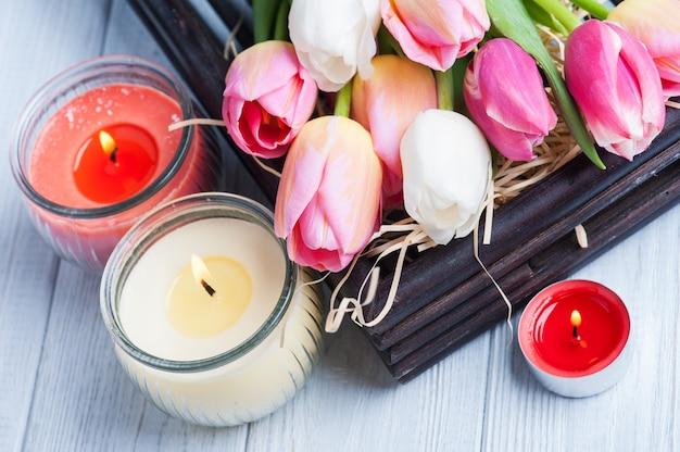 Gelbe und rosa duftkerzen mit tulpen