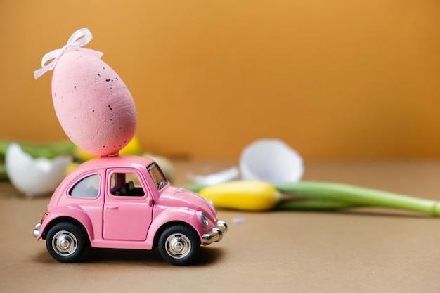 Gelbe und rosa retroautos mit eiern auf den dächern auf einer braunen oberfläche