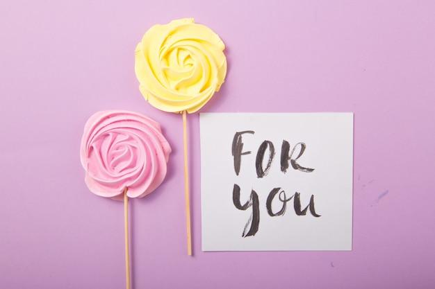Gelbe und rosa rosensüßigkeit in den pastellfarben auf einem holzstab mit karte