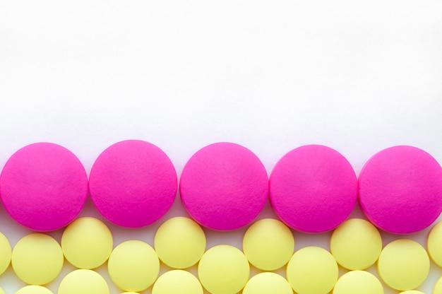 Gelbe und rosafarbene pillen auf einem weißen hintergrund.
