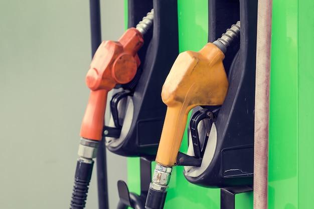 Gelbe und rote benzinzapfsäulen in einem tankstellenhintergrund grün, kraftstoffdüse in der ölstation thailand