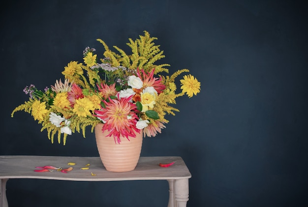 Gelbe und rote blumen in der vase auf vintage-regal