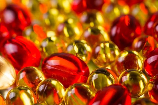Gelbe und rote medizinische kapseln auf einer spiegeloberfläche