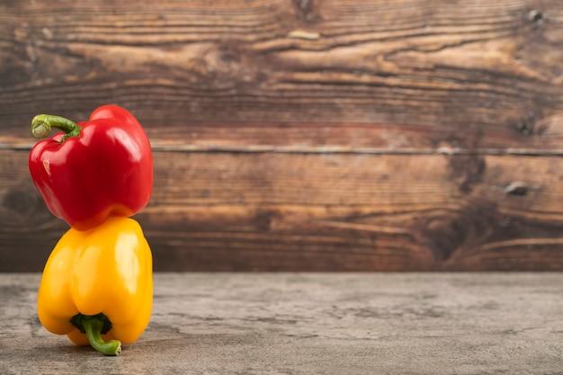 Gelbe und rote paprika auf steinoberfläche gelegt