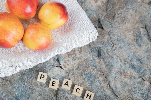 Gelbe und rote pfirsiche auf einem stück weißem handtuch.