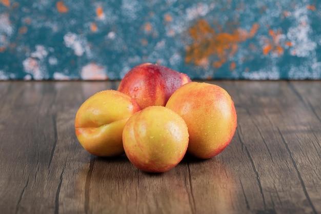 Gelbe und rote pfirsiche auf holztisch.