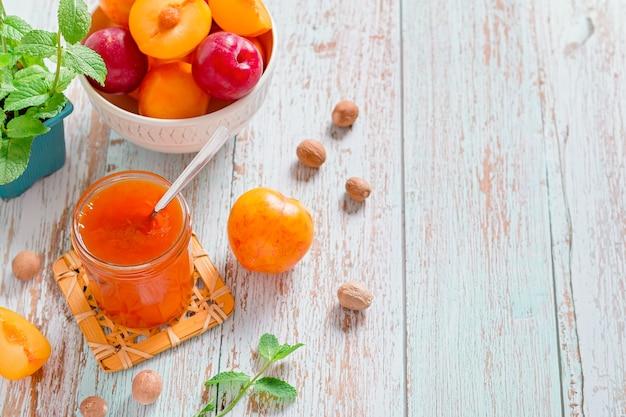 Gelbe und rote pflaumen in einem teller und einem glas pflaumenmarmelade auf abgenutztem holztisch flach, herbstfrucht konserviert konzept, kopierraum