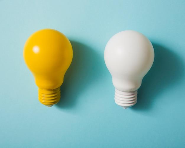 Gelbe und weiße glühlampe auf blauem hintergrund