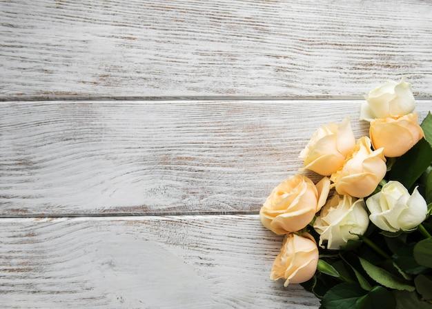 Gelbe und weiße rosen auf einem alten holztisch