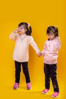 Gelbe wand. zufriedene ungewöhnliche schwestern mit genetischer störung, die ihre hände verbinden, während sie unter lichtern stehen