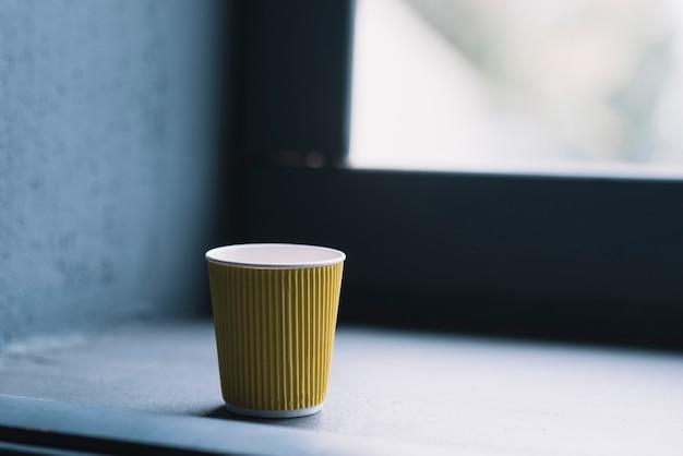 Gelbe wegwerfbare kaffeetasse nahe dem fensterbrett