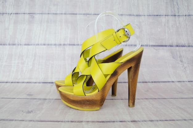 Gelbe weibliche sandalen auf einem holztisch