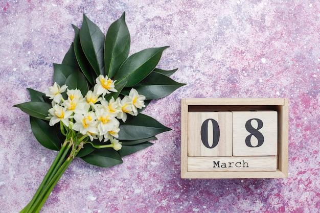 Gelbe weiße narzisse, narzisse, jonquilleblume auf rosa beton. 8. märz frauentag.