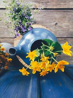 Gelbe wilde blumen in einer draufsicht des blauen topfes