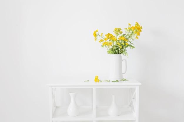 Gelbe wilde sommerblumen im krug auf weißem weinleseinnenraum