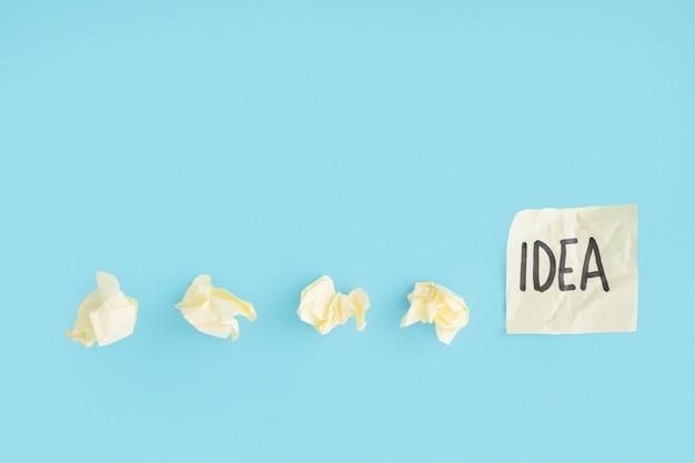 Gelbe zerknitterte papiere mit ideentext auf der klebrigen anmerkung über dem blauen hintergrund