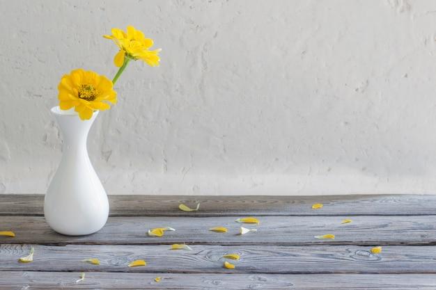 Gelbe zinnie in der weißen vase auf holztisch