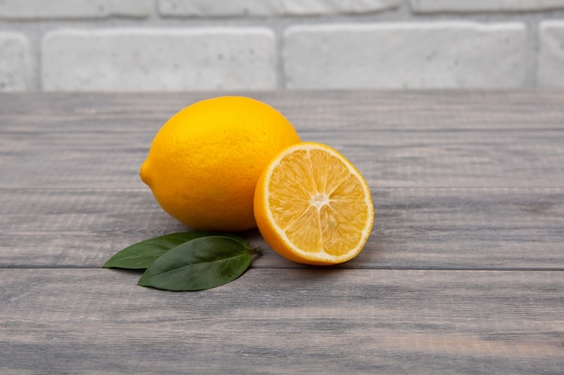 Gelbe zitrone auf einem hölzernen hintergrund. natürliches vitamin, anti-influenza und antiviraler inhaltsstoff.