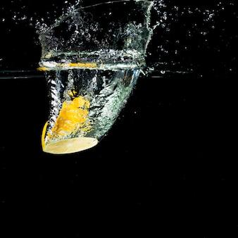 Gelbe zitrone, die in wasserspritzen fällt