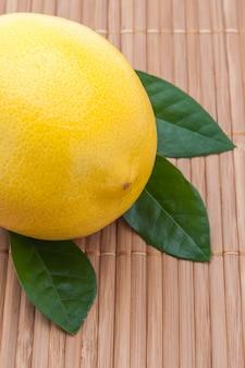 Gelbe zitrone mit grüner blattnahaufnahme auf bambusmatte.