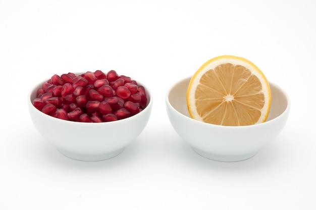 Gelbe zitrone und rote samen des granatapfels in den schalen auf einem weißen hintergrund.