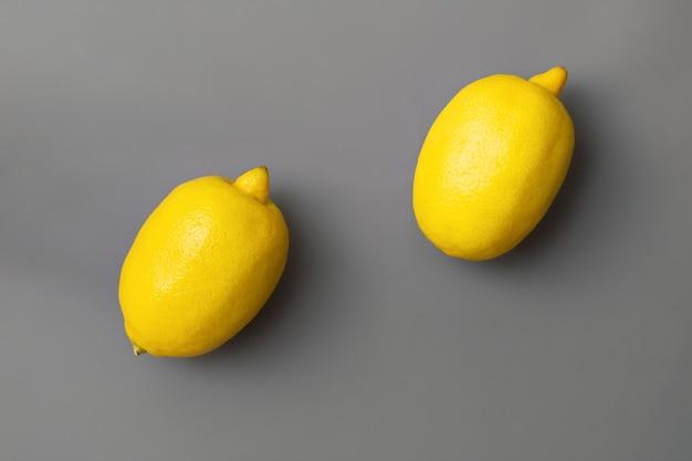 Gelbe zitronen auf grauem hintergrund. farben des jahres 2021 pantone illuminating und ultimate grey. flach liegen. speicherplatz kopieren