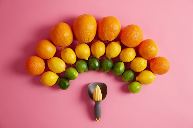 Gelbe zitronen der frischen orangen und grüne limetten im halbkreis über dem manuellen entsafter angeordnet. quetscher zur herstellung von bio-saft aus zitrusfrüchten. konzept der vitamine und des gesunden lebensstils.