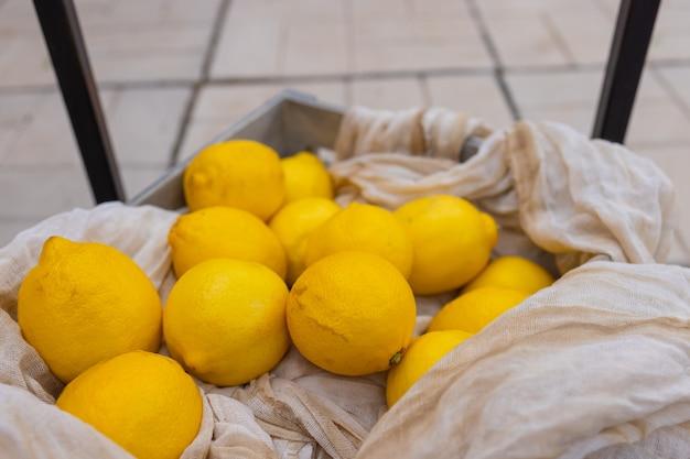 Gelbe zitronen in der tasche - netz auf weißer leinentischdecke.