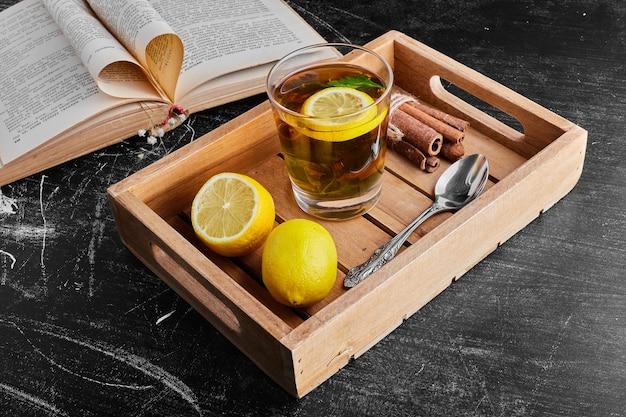 Gelbe zitronen isoliert auf schwarzer oberfläche mit einem glas getränk in einem holztablett.