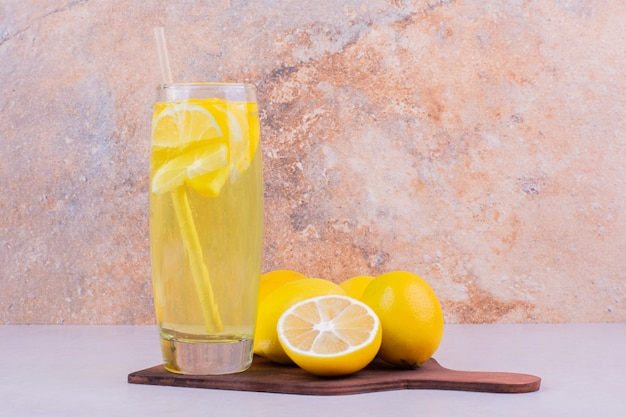 Gelbe zitronen mit einem glas limonade.