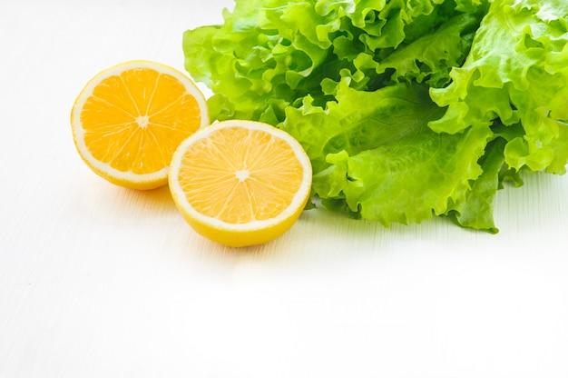 Gelbe zitronenhälfte und grüner blattkopfsalat auf weißem holztisch und teils lokalisiert
