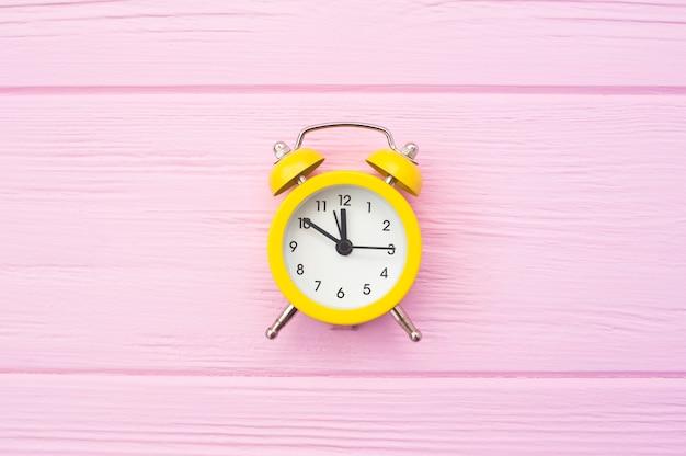 Gelber alter artwecker auf rosa hölzernem hintergrund mit platz für ihren text