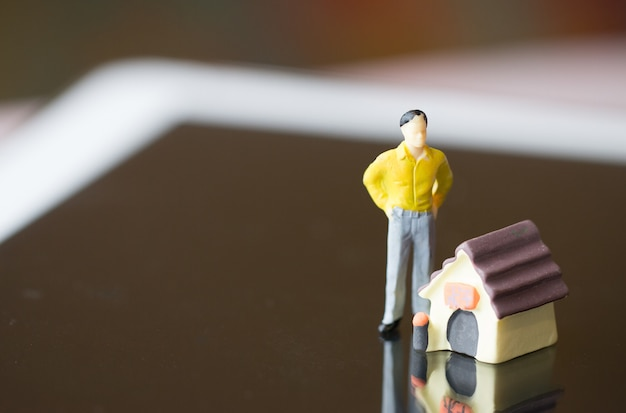 Gelber anzug der miniaturgeschäftsleute, der nahes miniaturhaus auf tablette für verkaufshändler, immobilienimmobilieninvestition steht