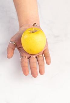 Gelber apfel in den händen auf einer marmorwand