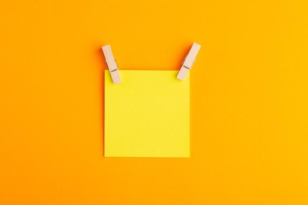 Gelber aufkleber der draufsicht leer auf der orange oberfläche