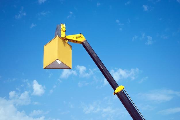 Gelber ausleger des mobilkrans mit einem aufgehängten würfel für werbung