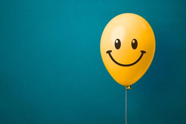 Gelber ballon mit glücklichem gesicht. freude und glückskonzept