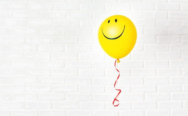 Gelber ballon mit lächeln hängt aganst weiße wand