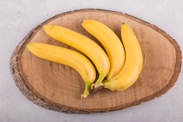 Gelber bananenbündel lokalisiert auf beton auf einem stück holz