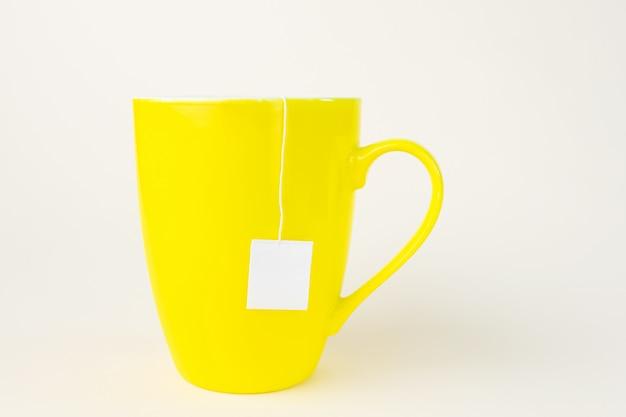 Gelber becher mit teebeutel. aus dem becher ragt ein weißes etikett heraus.
