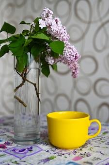 Gelber becher nahe einer vase mit einer pflanze