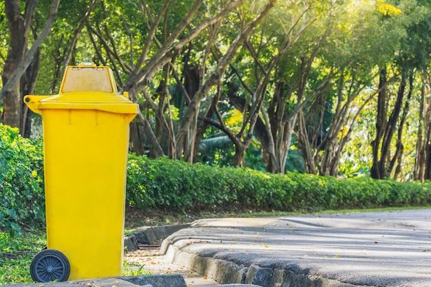 Gelber behälter im park im herbst benutzt für das platzieren des textes