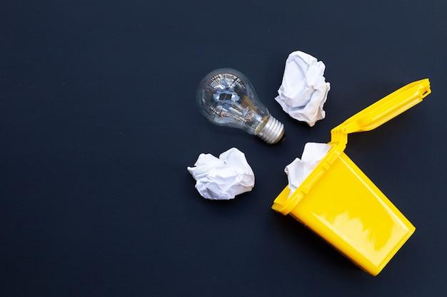 Gelber behälter mit glühbirne und weißem zerknittertem papier an dunkler wand. ideen und kreatives denkkonzept. draufsicht