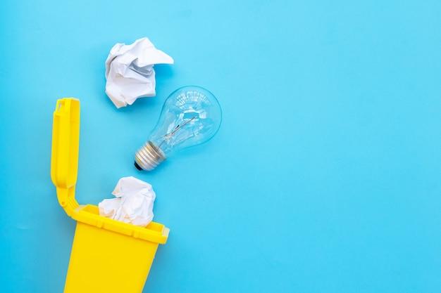Gelber behälter mit glühbirne und weißem zerknittertem papier auf blauem hintergrund. ideen und kreatives denkkonzept. draufsicht