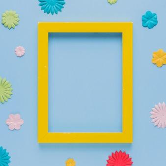 Gelber bilderrahmen umgeben mit schönem blumenausschnitt