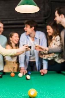 Gelber billardball mit einer nummer auf snookertabelle vor freunden, die wein rösten