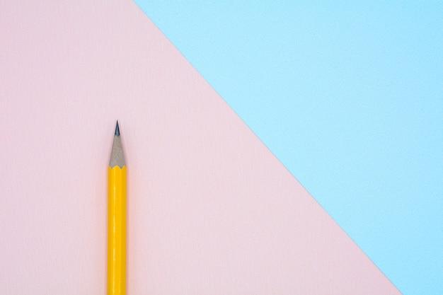 Gelber bleistift auf blauem und rosa papier
