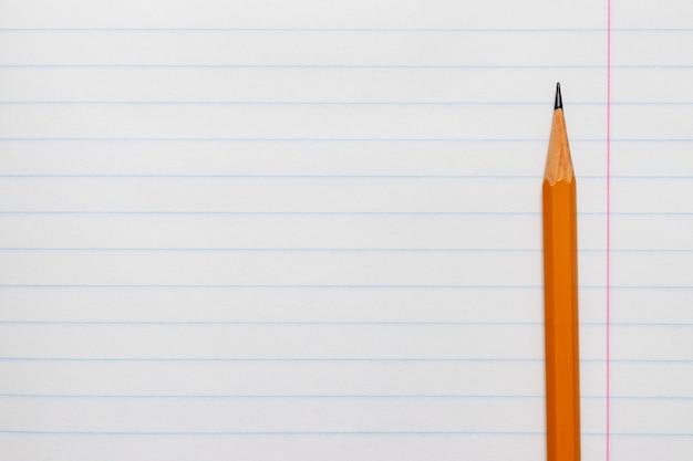 Gelber bleistift auf dem hintergrund eines weiß gezeichneten blattes des notizbuches