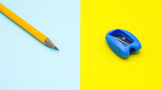 Gelber bleistift und ein blauer plastikbleistiftspitzer auf blauem und gelbem hintergrund
