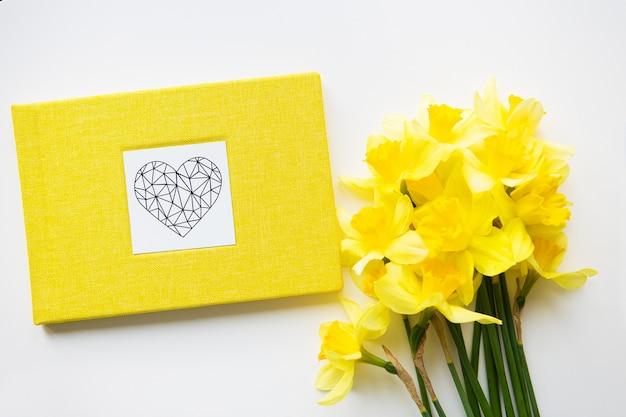 Gelber blumenstrauß von narzissen und von gelbem buch auf weißer tabelle